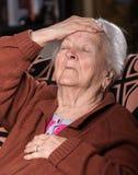 Vieja mujer canosa que sufre de dolor de cabeza Fotos de archivo