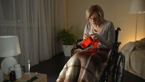 Vieja mujer cansada en los vidrios que llevan de la silla de ruedas que intentan hacer punto, vista pobre almacen de video