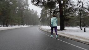 Vieja mujer cauc?sica mayor que corre en el parque nevoso en invierno con los auriculares Detr?s siga el tiro almacen de video