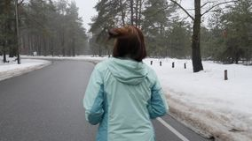 Vieja mujer cauc?sica mayor que corre en el parque nevoso en invierno con los auriculares Detr?s siga el tiro C?mara lenta almacen de metraje de vídeo