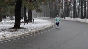 Vieja mujer cauc?sica mayor que corre en el parque nevoso en invierno con los auriculares Front Static Shot C?mara lenta almacen de video