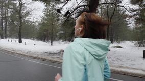 Vieja mujer cauc?sica mayor que corre en el parque nevoso en invierno con los auriculares El lado trasero sigue el tiro C?mara le almacen de metraje de vídeo