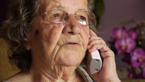 Vieja mujer jubilada que habla en el teléfono metrajes