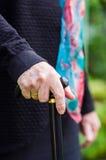 Vieja mujer mayor con la bufanda que camina con el palillo foto de archivo