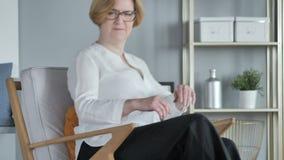 Vieja mujer mayor creativa que viene y que se sienta en el sofá metrajes