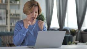Vieja mujer mayor emocionada que celebra el éxito, trabajando en el ordenador portátil almacen de metraje de vídeo