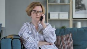 Vieja mujer mayor enojada que habla en el teléfono, sentándose en el sofá en dormitorio almacen de metraje de vídeo