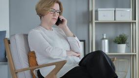 Vieja mujer mayor que habla en el teléfono, sentándose en el sofá en dormitorio almacen de video