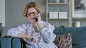 Vieja mujer mayor que habla en el teléfono, sentándose en el sofá en dormitorio almacen de metraje de vídeo