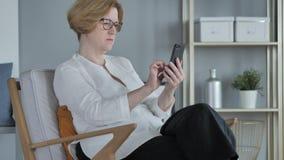 Vieja mujer mayor que hojea en Smartphone, usando Internet almacen de video