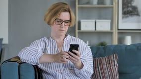 Vieja mujer mayor que hojea en Smartphone, usando Internet metrajes