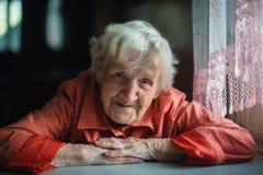 Vieja mujer solitaria que se sienta cerca de ventana Fotos de archivo libres de regalías