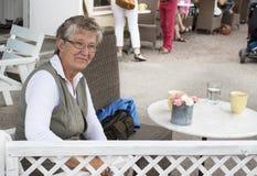 Vieja mujer sonriente en café Fotos de archivo