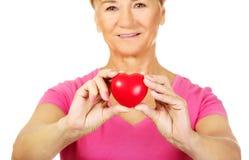 Vieja mujer sonriente que lleva a cabo el corazón rojo del juguete Fotografía de archivo libre de regalías