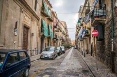Vieja opinión de la calle del estrecho de la ciudad de Cefalu con los coches parqueados y los pequeños balcones en la mañana Fotografía de archivo
