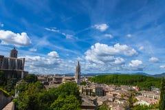 Vieja opinión de la ciudad de Girona con las montañas verdes y el cielo azul con las nubes Foto de archivo libre de regalías