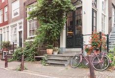 Vieja opinión típica de la calle de la ciudad de Amsterdam con los edificios tradicionales y la bicicleta del vintage foto de archivo