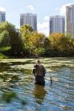 Vieja pesca del pescador en un lago o un río con una caña de pescar en un día soleado Hombre que se coloca en el agua Imagen de archivo libre de regalías