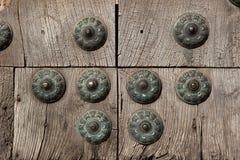 Vieja puerta de madera fijada con los remaches de cobre amarillo grandes Imagen de archivo libre de regalías