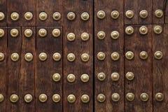 Vieja puerta de madera fijada con los remaches grandes del latón en Córdoba, España Imagen de archivo libre de regalías