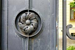 Vieja puerta del metal con la flor del hierro labrado fotos de archivo