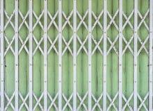 Vieja puerta plegable de la puerta del metal (obturador del laminado de acero) - pocilga del vintage fotografía de archivo libre de regalías