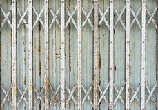 Vieja puerta plegable de la puerta del metal (obturador del laminado de acero) - pocilga del vintage imagen de archivo