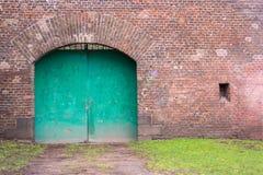 Vieja puerta verde y pared de ladrillo roja Fotos de archivo libres de regalías