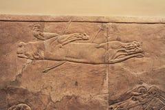 Vieja relevación asiria de un beig del león buscado imagen de archivo