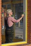 Vieja renovación de la tienda, ventana de la pintura de la mujer foto de archivo