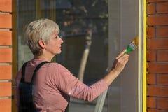 Vieja renovación de la tienda, ventana de la pintura de la mujer imagen de archivo libre de regalías