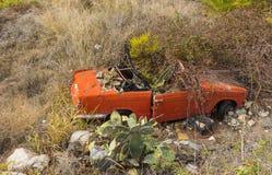 Vieja ruina del coche que se coloca al lado de un camino abajo de la colina en Andalucía Imagenes de archivo
