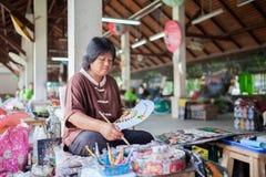 Vieja sentada asiática de la mujer, pintura una fan Imágenes de archivo libres de regalías