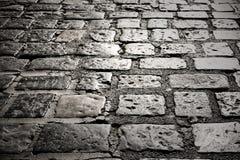 Vieja superficie de la carretera de la piedra del adoquín que pavimenta textu oscuro del fondo de la noche Imagen de archivo
