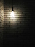 Vieja textura de cerámica blanca de la pared con una luz oscura del bulbo Fotos de archivo libres de regalías