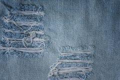 Vieja textura de la mezclilla con un agujero fotos de archivo
