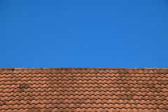 Vieja textura roja de las tejas de tejado y fondo del cielo azul Imágenes de archivo libres de regalías
