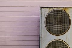 Vieja unidad del sistema de enfriamiento de la CA del acondicionador de aire con la pared rosada imagenes de archivo