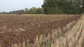 Vieja vuelta del tractor encima del suelo arable del arado en otoño 4K metrajes