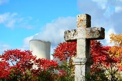 Vieja y resistida cruz de piedra cristiana con una central nuclear en fondo Fotografía de archivo libre de regalías