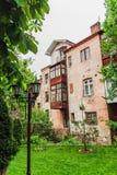 Vieja yarda hermosa antigua con las casas viejas del vintage, árboles verdes e hierba, entonados Fotos de archivo