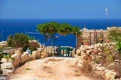 Vieja yarda maltesa de la casa de planta baja con la cerca de piedra y el cano vid-cubierto Foto de archivo