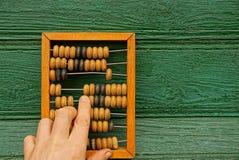 Viejas cuentas de madera y una mano con un finger foto de archivo