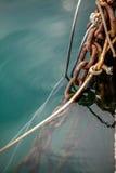 Viejas cuerdas y cadenas oxidadas del amarre en la agua de mar Imagen de archivo