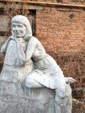 Viejas esculturas abandonadas en un parque descuidado entrelazado con las plantas, hojas caidas, el concepto de edad imagen de archivo libre de regalías