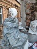 Viejas esculturas abandonadas en un parque descuidado entrelazado con las plantas, hojas caidas, el concepto de edad imagen de archivo
