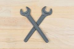 Viejas llaves inglesas cruzadas en una tabla de madera imagenes de archivo