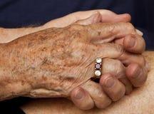 Viejas manos de la explotación agrícola de los pares con el anillo fotos de archivo libres de regalías