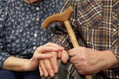 Viejas manos de los pares con el bastón imagen de archivo