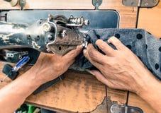 Viejas manos de trabajo en la máquina de coser Imágenes de archivo libres de regalías